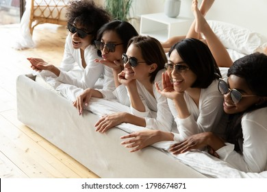 Funny diverse girls wearing stylish trendy sunglasses equal bathrobes lying in bed. Ladys posing photographing in hotel bedroom. After spa procedures five women enjoy photoshoot celebrating hen-party