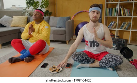 Funny diverse male friends meditating together at home training. Cunning bearded freak guy eating sweet cookie without being seen. Fun and entertainment.