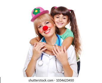 Funny doctor wearing clown outfit with a happy child patien