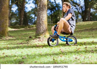 Funny downhill on small kids balance bike. Young crazy man riding down from high hill.