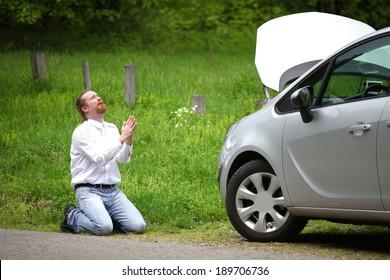 Der lustige Fahrer betet ein kaputtes Auto auf der Straße