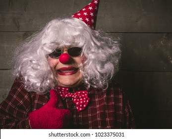 Funny droll silly clown with blonde wig and red nose