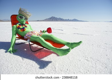 Funny drunk green alien tourist goes on cheap holiday relaxing in beach chair with tropical drink