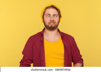 Funny dumb hipster bearded guy in beanie hat and checkered shirt making silly face with eyes crossed, looking at camera stupid brainless expression. indoor studio shot isolated on yellow background