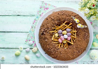 Funny Easter cake in the form of a bird nest with a speckled egg, Easter food on green wooden background top view