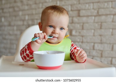 funny eating baby with durty face on the high chair
