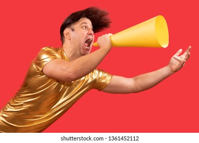 An funny eccentric man screaming to a megaphone on the red background. Cheerful crazy showman hold an speaker.