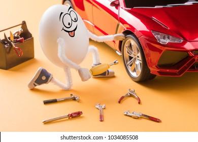 Funny egg mechanic repair the car wheel.