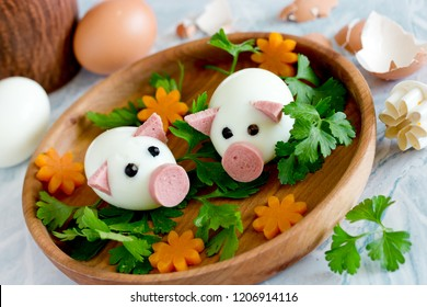 Funny egg pigs on wooden plate with carrot flowers and green parsley, food art idea for healthy kids snack
