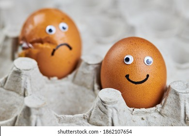 Funny egg and sad cracked egg in paper egg tray. Two easter chicken eggs, fresh and natural. Delivery concept, copy space.