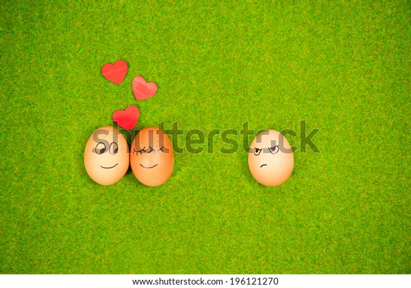 funny eggs in love and one jealous egg on a green grass. summer romantic