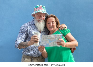 Funny elderly couple of tourist reading a paper map. He is wearing a flowery hat and he is holding a cardboard cup.