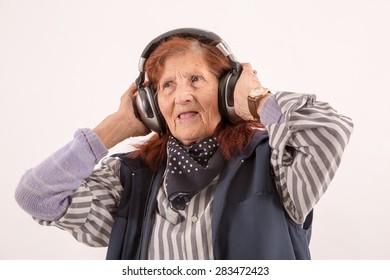 Funny Elderly lady listening music with headphones