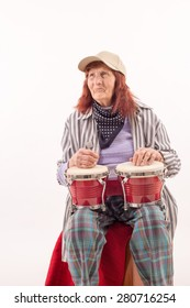 Funny elderly lady makes music with a wooden bongo.