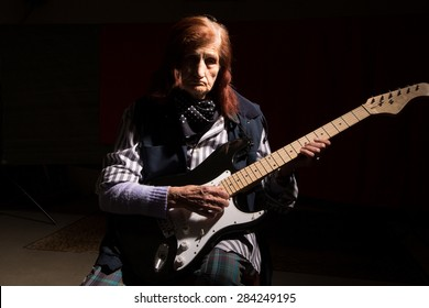Funny elderly lady plays electric guitar in a dark room.