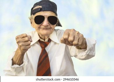 Funny elderly woman wearing cap and eyeglasses in a fight pose. Selective focus.