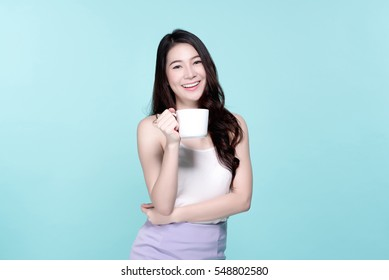 Funny emotion of asian young beautiful woman drink hot coffee, beauty face natural makeup, isolated over blue background.