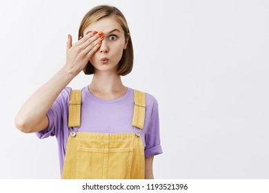 Funny emotive girl peeking, reading sign with one eye, trying check sight, standing in trendy yellow overalls, covering half of face with palm, folding lips, gazing at camera intrigued and interested