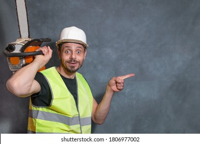 Funny European man with a chainsaw. Work clothes, hard hat. The man points his finger. A bright emotion. Copy space.
