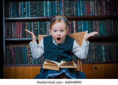 Funny excited girl sitting with opened book in a library. Educational concept.