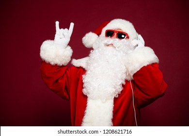Funny and excited Santa Claus is listening music in headphones and sunglasses. Happy New Year, Merry Christmas, Celebration concept, travel, trips, party time, isolated on red background