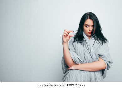 Funny excited woman showing something very tiny little size by fingers, happy girl with open mouth amazed by small prices looking at camera isolated on white grey studio background.