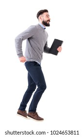 Funny excited young smart casual business man running with notebook in hands. Full body length portrait isolated on white studio background.