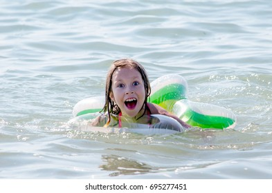 funny expression on a  happy swimming girl in lake Michigan