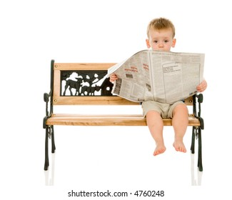 Funny expression on a two year old toddler boy as he reads the Newspaper. He may be peeking up in surprise after checking his stock portfolio.  Newspaper prop is blurry so that no text is legible.