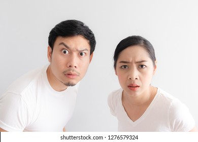 Funny face of Asian lovers couple in doubt at an unbelievable thing that they are looking at
