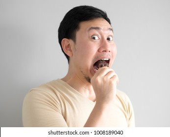 Funny face Asian man eat chocolate vanilla ice pop.