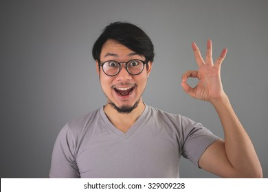 Funny face Asian man is showing an Okay sign.