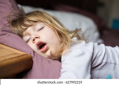 funny face expression with open mouth of blonde caucasian three years old child,  sleeping on  king bed