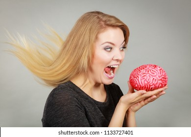 Funny face expressions, fooling around concept. Crazy woman holding brain wanting to eat it