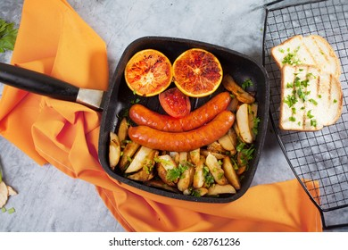Funny face from food Potatoes, sausages, tomato, oranges, grill, frying pan, top view, creative