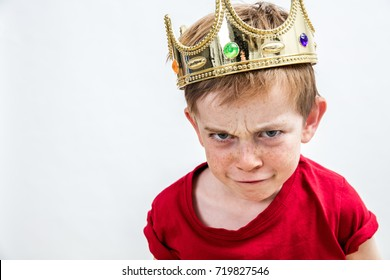 funny face of a little boy with sulking blue eyes and cute freckles wearing a king crown for mischievous humor and cheeky education, white background, copy space