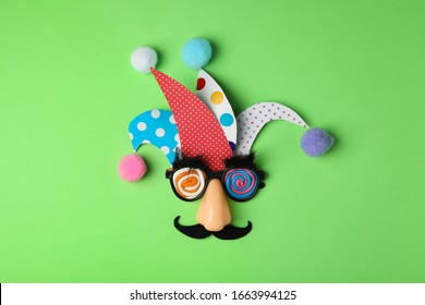 Funny face made of party items on green background, flat lay. April Fool's Day
