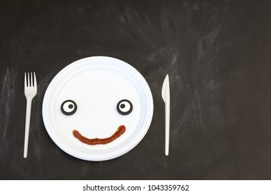 Funny face on a plate.. Concept of dietary restrictions, weight loss, anti-obesity, healthy diet.