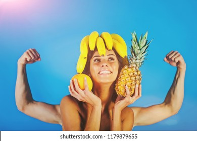 Funny face photo. Fresh fruit concept. Man and woman posing studio. Strong man. Pineapple. Summer fruits. Hot girls. Sexy couple. Happy woman face. Strong. Vegetables.