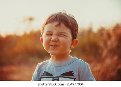 A funny face of a two years boy in the sunset lights on a summer day.