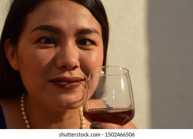 Funny faced, cross eyed beautiful middle aged woman holding wine glass close to her lips