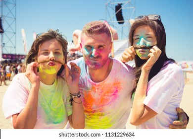 funny faces at holi party outdoor. young friends having fun at summer festival of  holi. faces covered with gulal powder the color dust. concept of unity, friendship joy and summertime outdoor party.