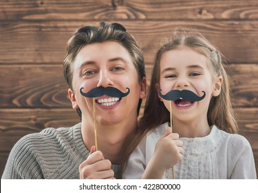 Funny family! Father and his child daughter girl with a paper accessories. Beauty funny girl holding paper mustache on stick. Beautiful young man holding paper mustache on stick.