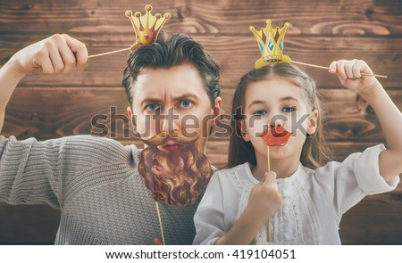 Funny family! Father and his child daughter girl with a paper accessories. Beauty funny girl holding paper lips and crown on stick. Beautiful young man holding paper beard and crown on stick.