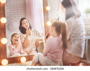 Funny family at home. Mother and her child girl are doing your makeup and having fun near mirror. Mom and daughter wear lipstick in kids room.
