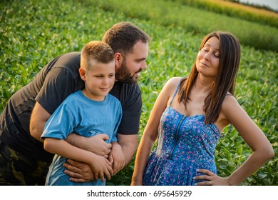 Funny family moments, family concept image. Father is hugging sun and mom is smiling while looking at them.