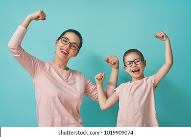 Funny family on a background of bright blue wall. Mother and her daughter girl. Mom and child are having fun. Pink and turquoise colors.