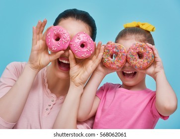 Funny family on a background of bright blue wall. Mother and her daughter girl are having fun with colorful donuts. Dieting concept and junk food. Yellow, pink and turquoise colors.