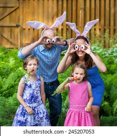 Funny family portrait on Easter of mother and father in bunny ears and silly eyes made from eggs as their children pose eating carrots outside in a garden during the spring season. Part of a series.