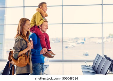 Funny family trip. Side view of young happy family going down hall to registration in airport going on holiday together